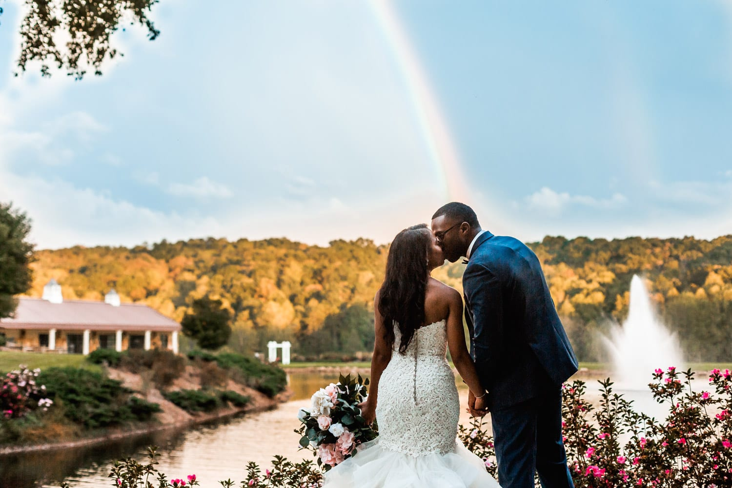 Bride and groom kiss in front of rainbow