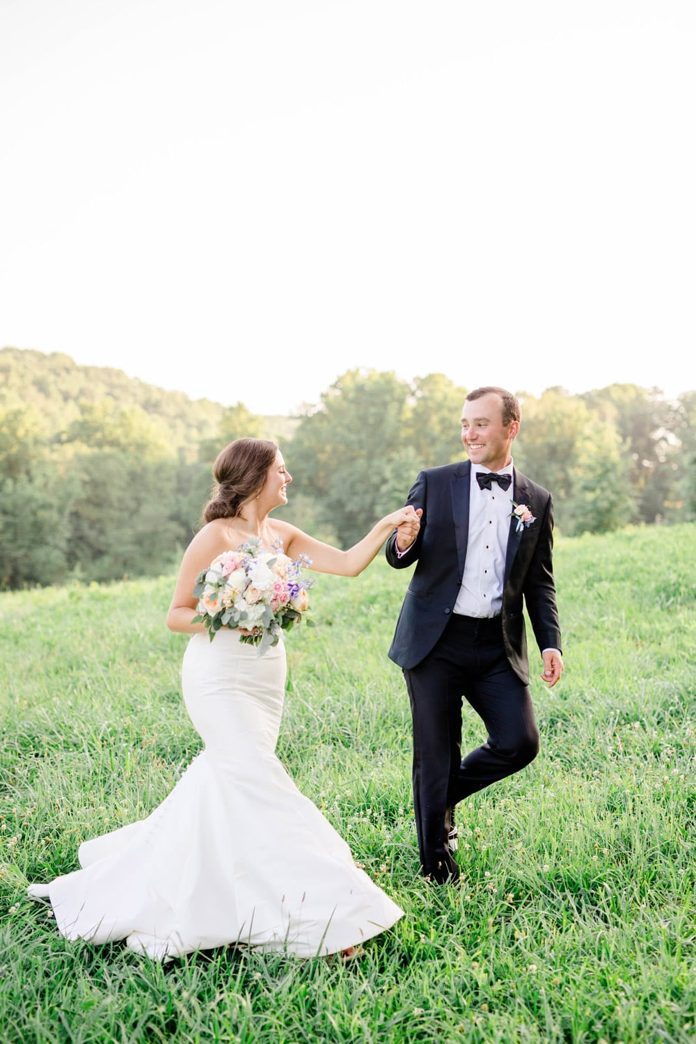 Groom leads bride through the pasture