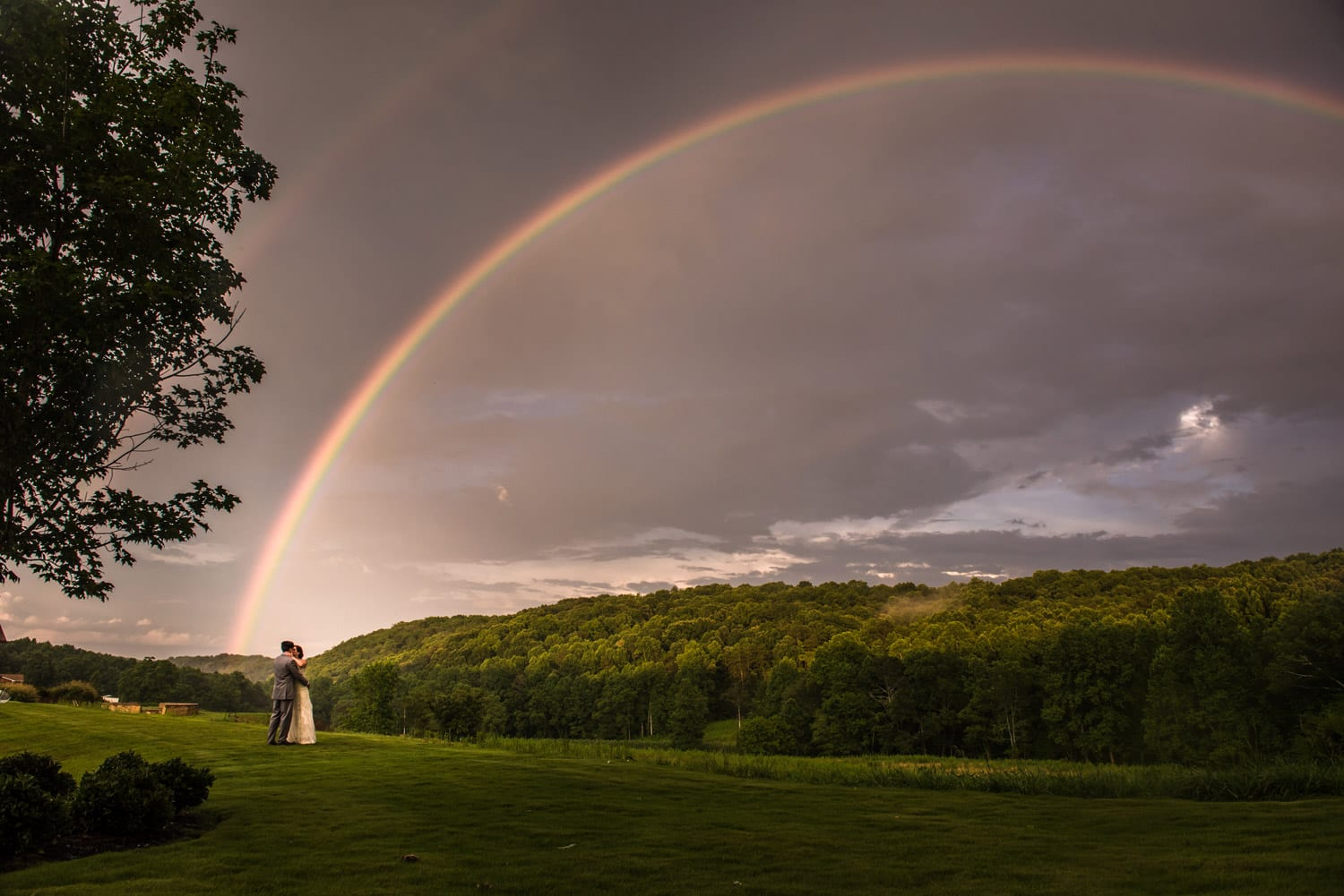 Bride and groom hold each other in front of rainbow