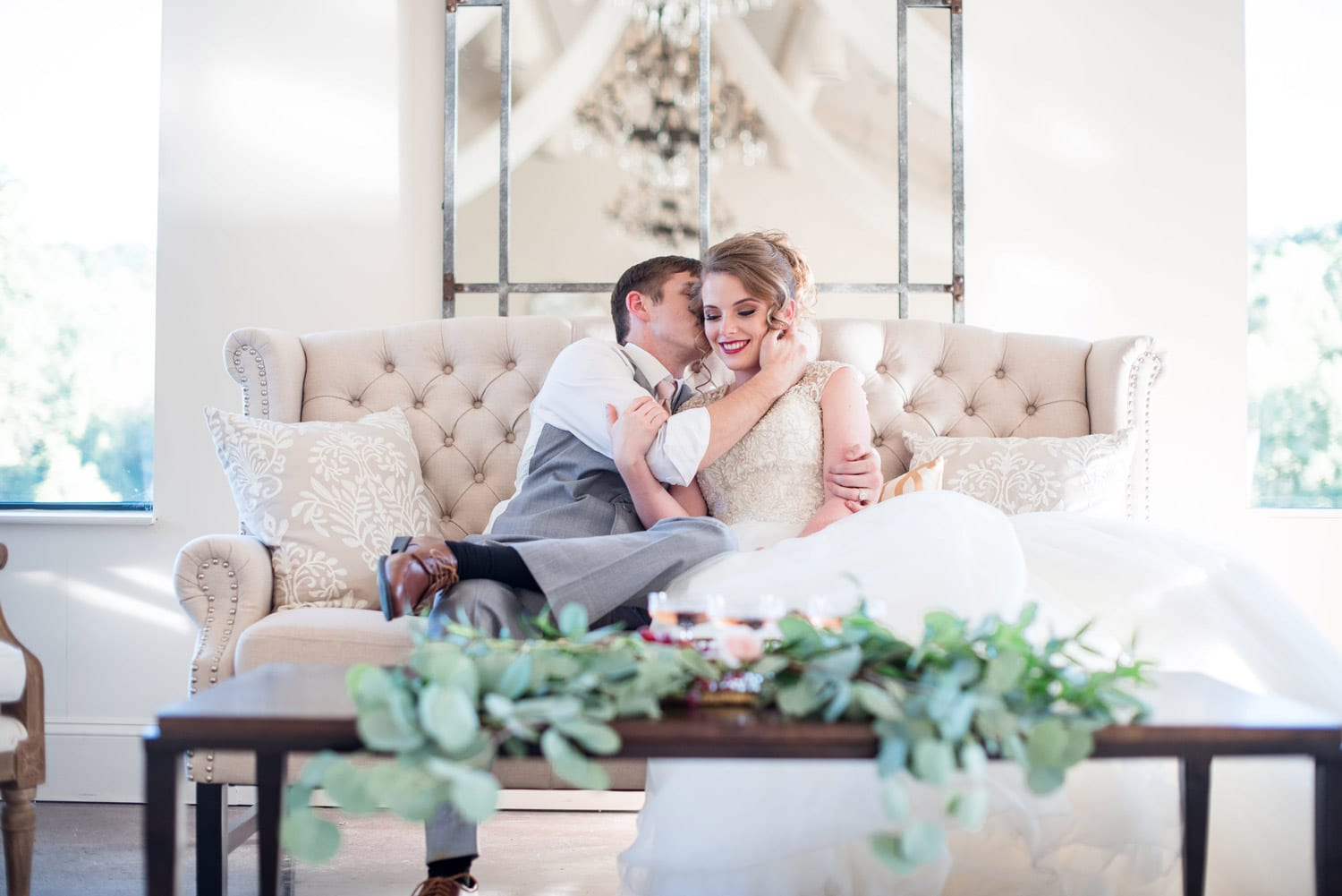 Bride and groom caress each other on love seat