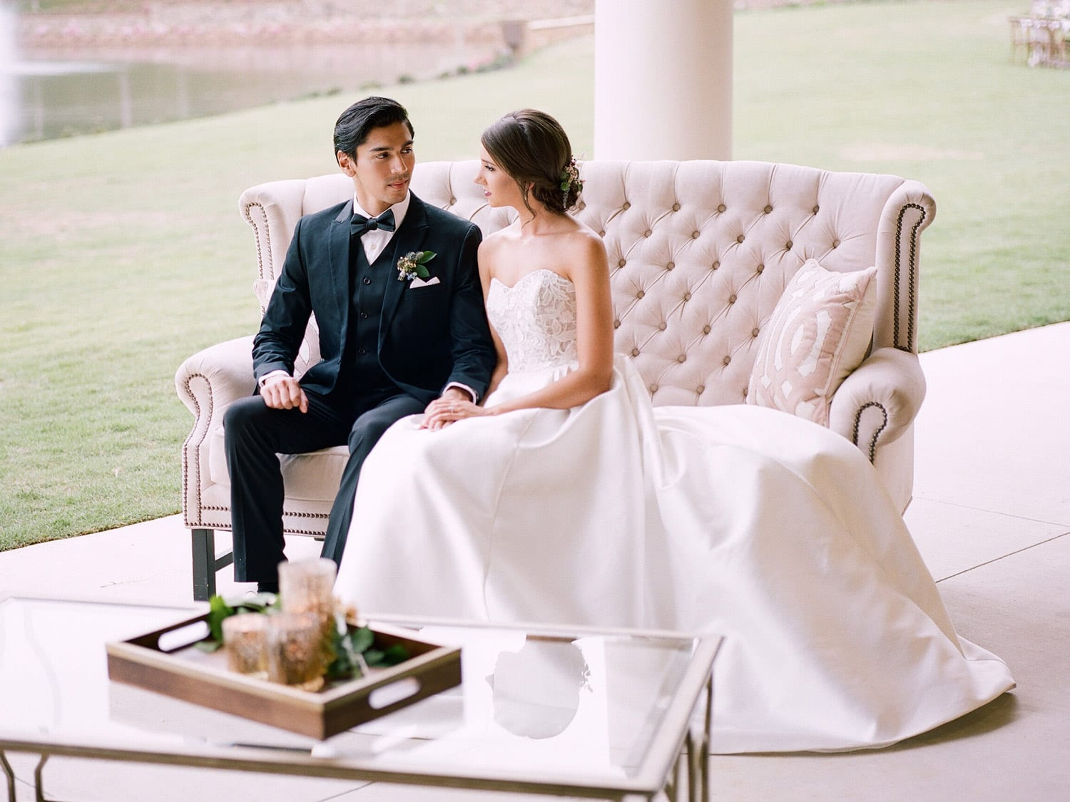 Bride and groom sit on love seat