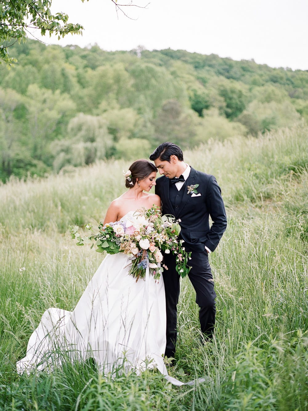 Bride and groom pose in pasture