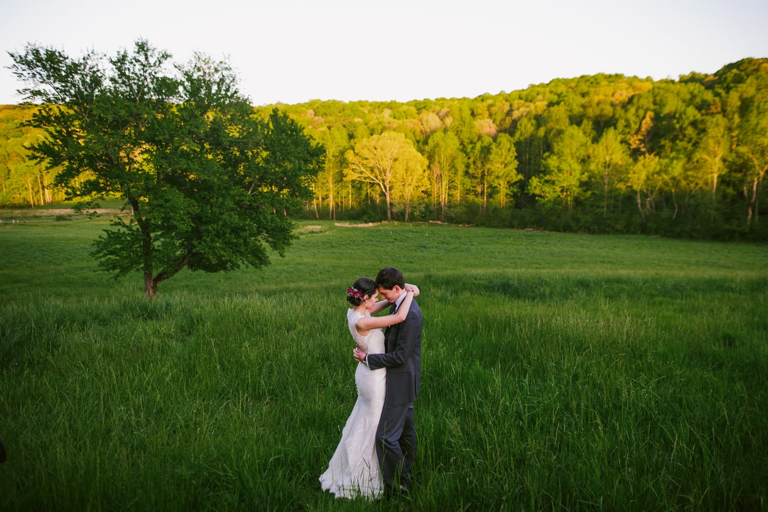 Bride and groom hold each other in the pasture
