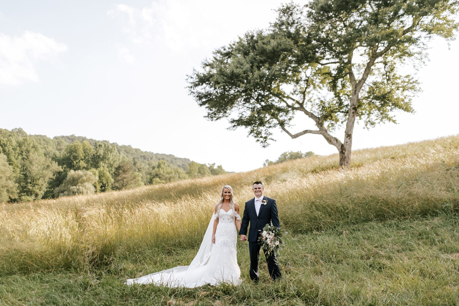 Bride and groom hold hands in pasture in front of tree