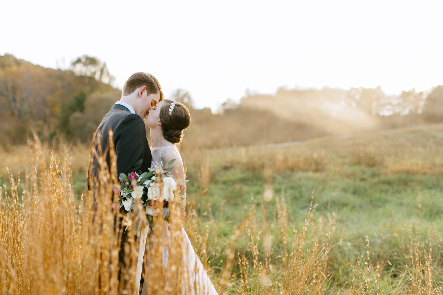Bride and groom kiss in pasture