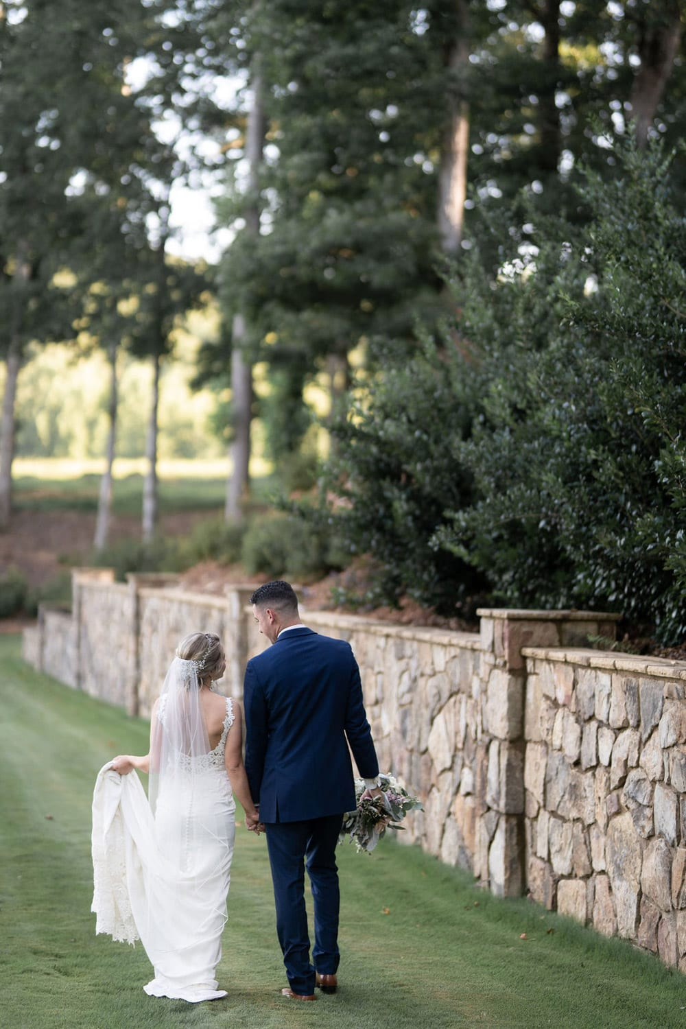 Bride and groom hold hands while walking along the water