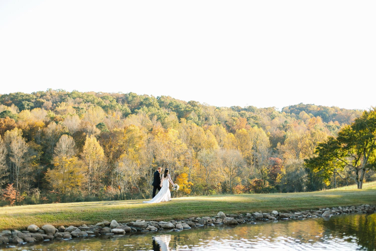 Bride and groom walk along the water while holding hands