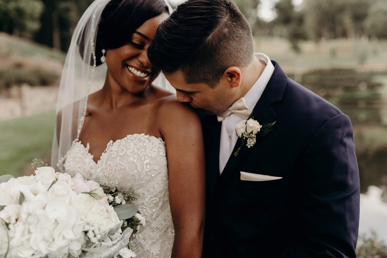Groom kisses bride's shoulder by the water