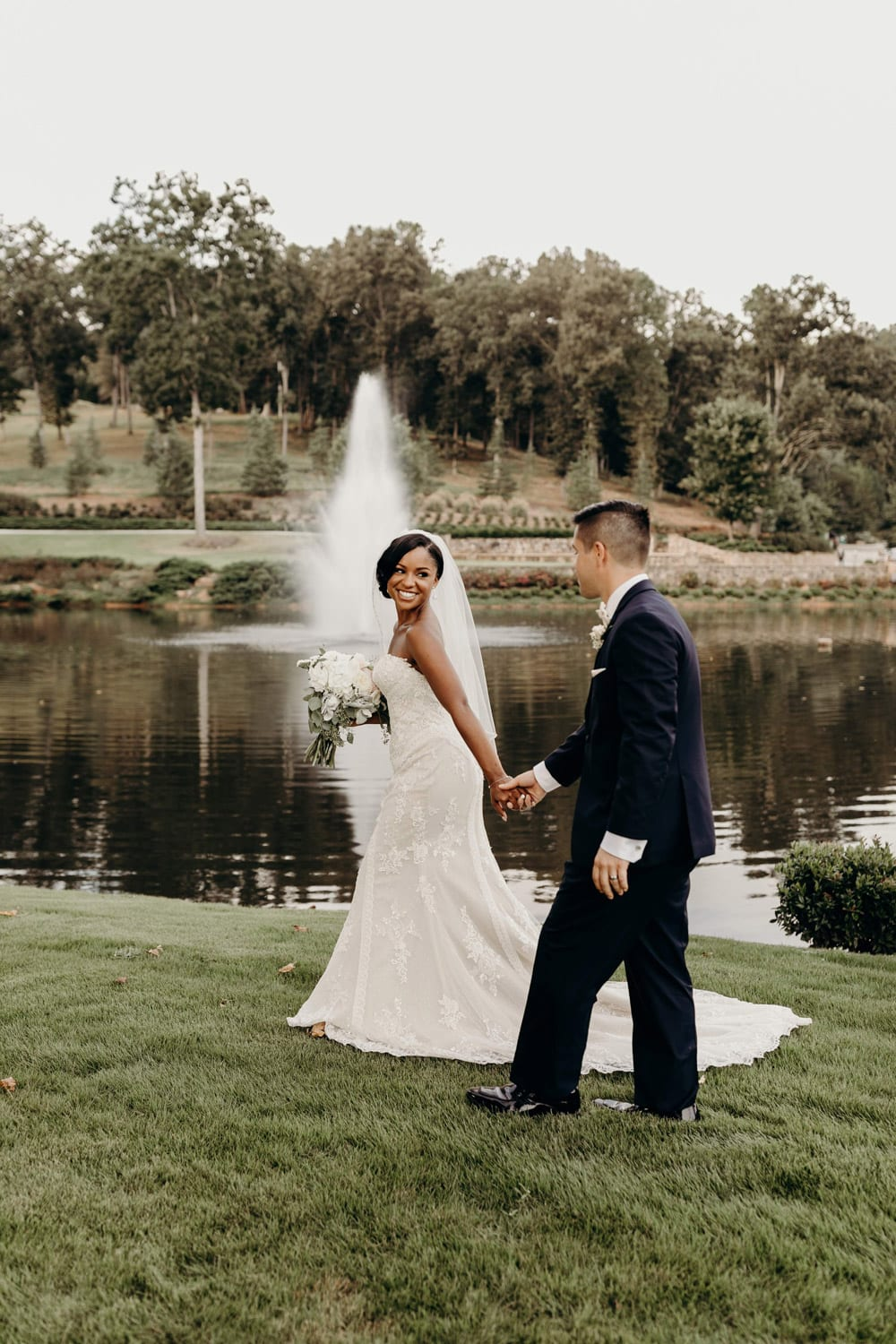 Bride leads groom by the hand in front of fountain