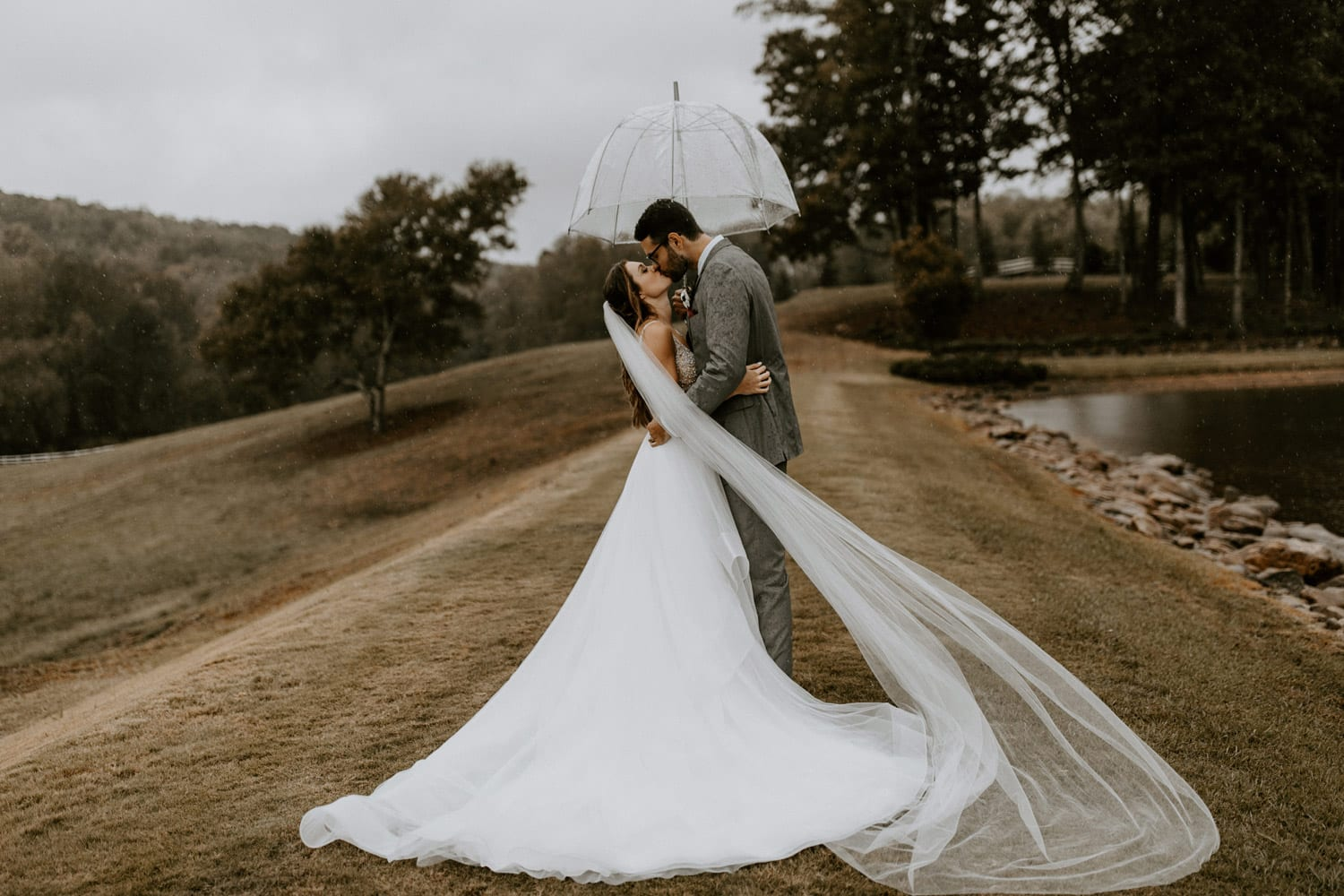 Bride and groom kissing in the rain outside with umbrella