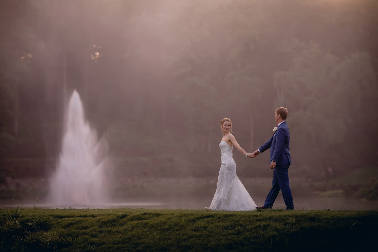 Bride leads groom by the fountain