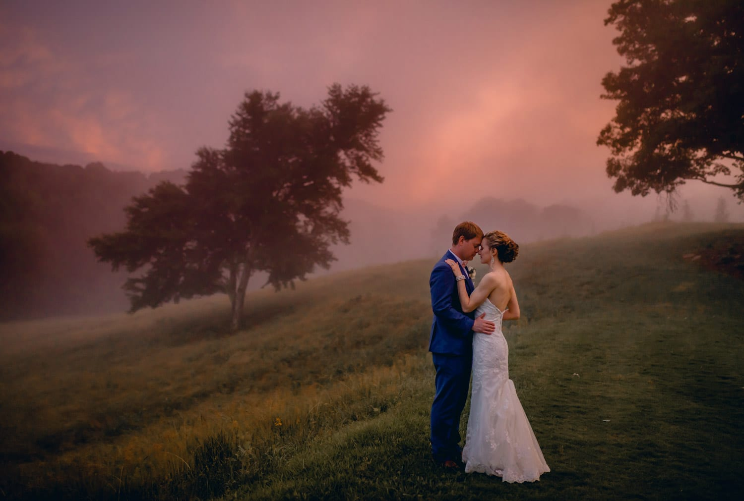 Bride and groom hold each other in front of pasture