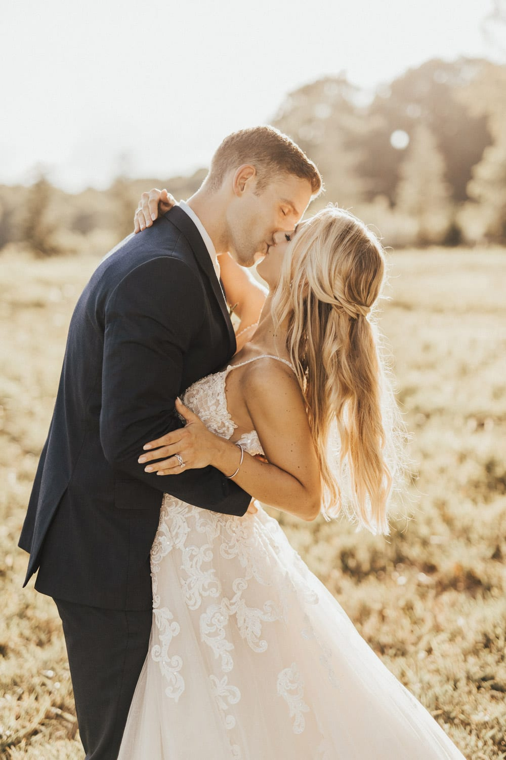 Bride and groom kiss in the pasture