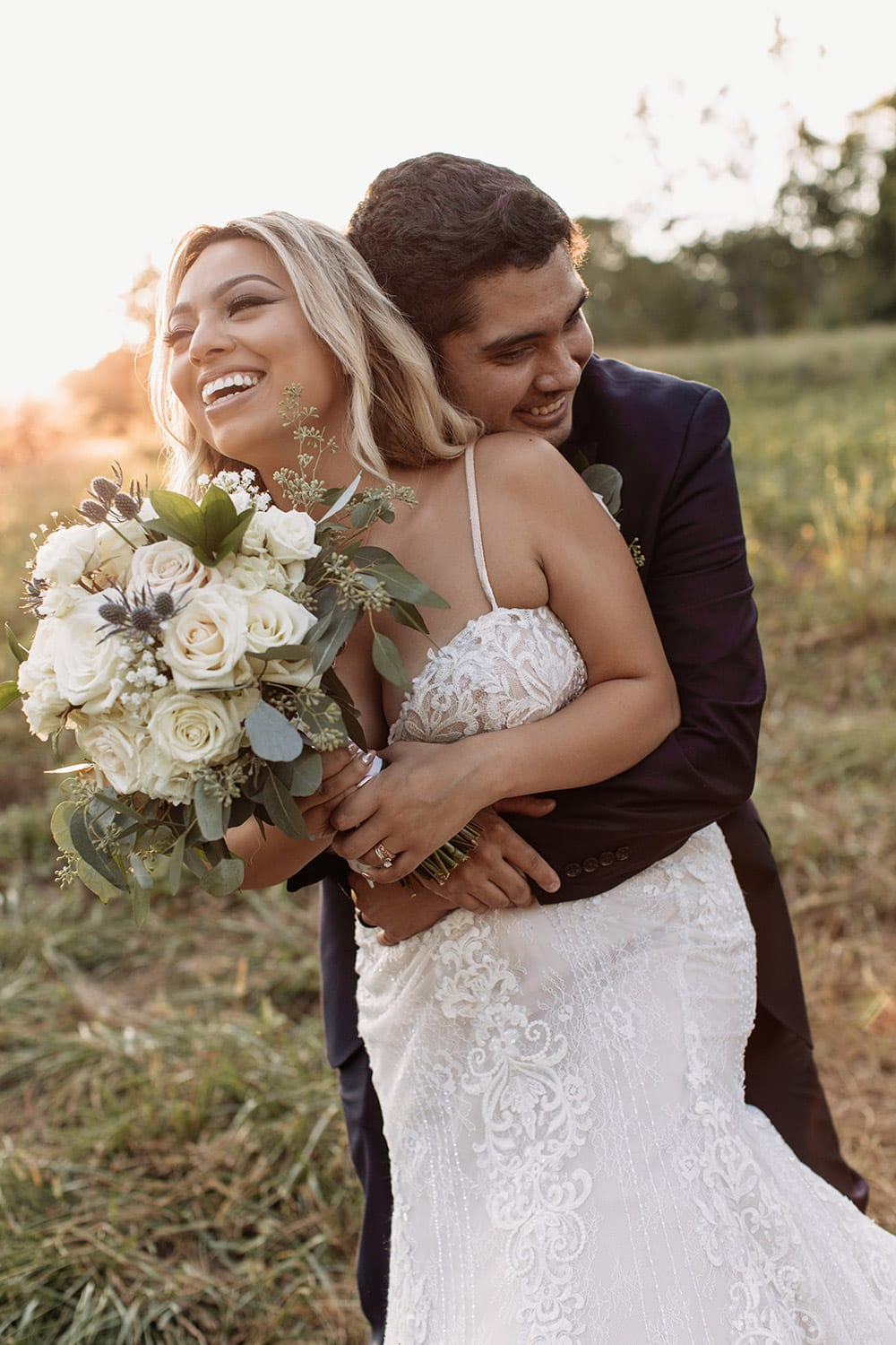 Groom holds bride in the pasture
