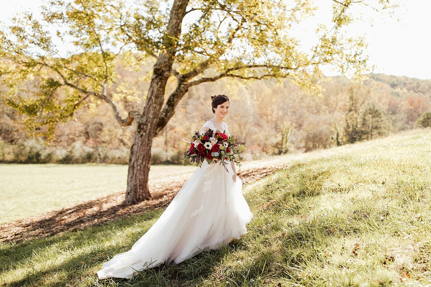 Bride walks in pasture with flowers by tree