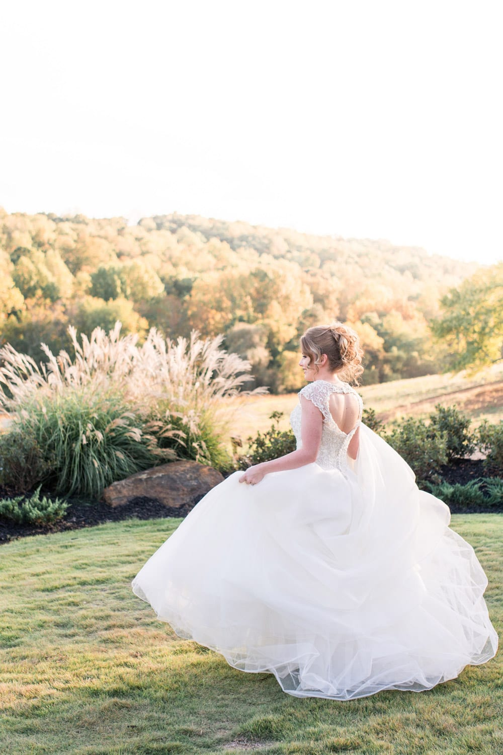 Bride walks outside in front of pasture