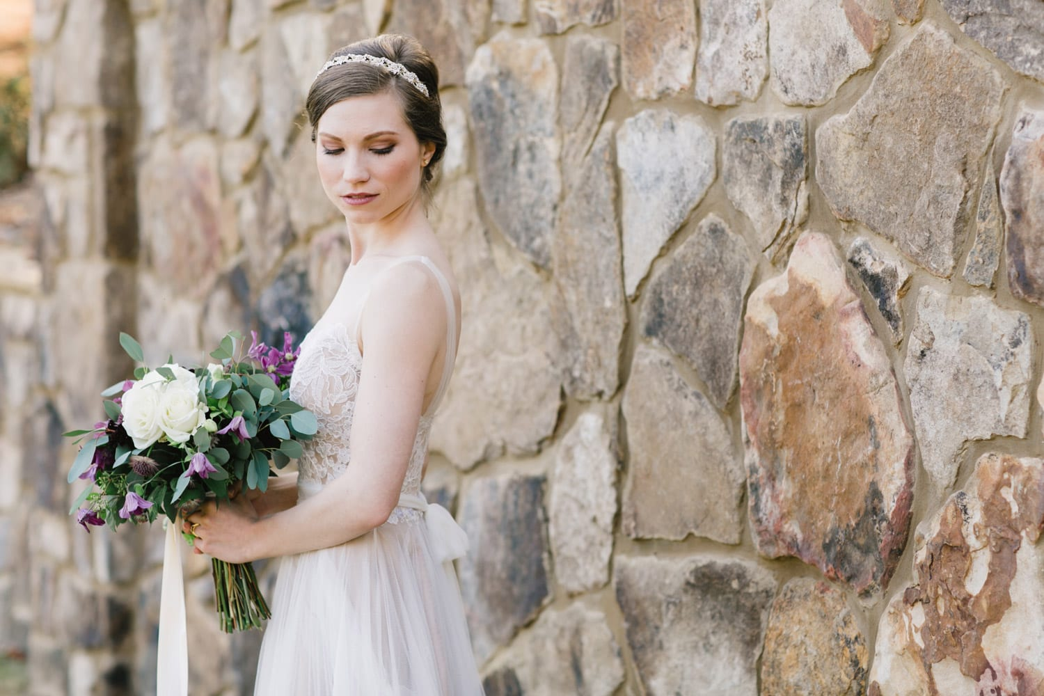 Bride poses with flowers in front of stone wall