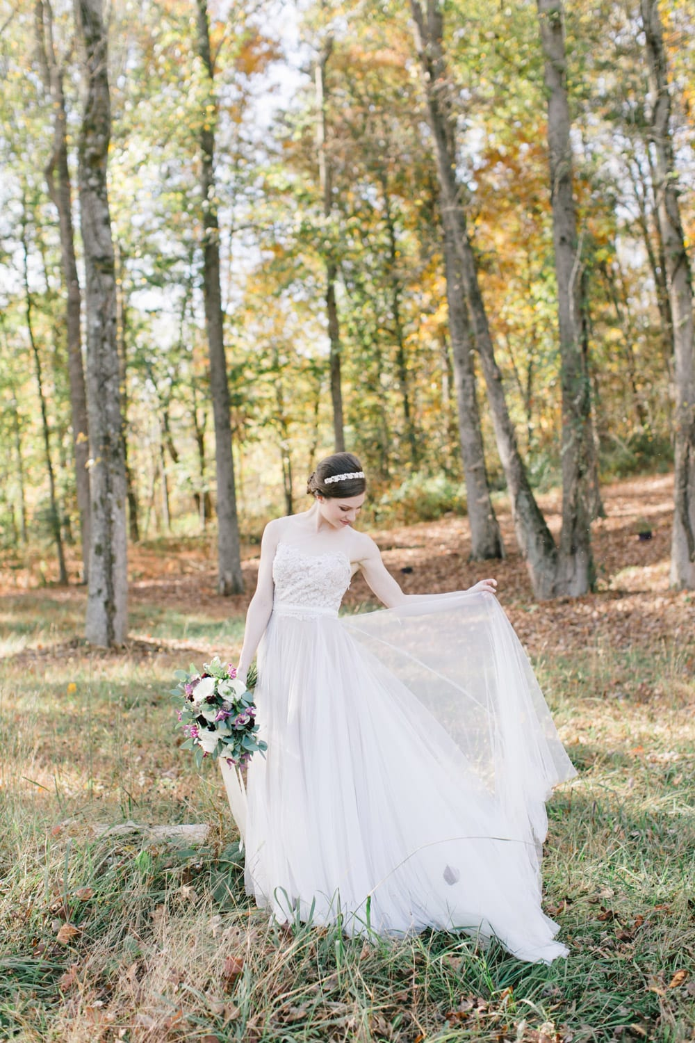 Bride stands in forest holding flowers