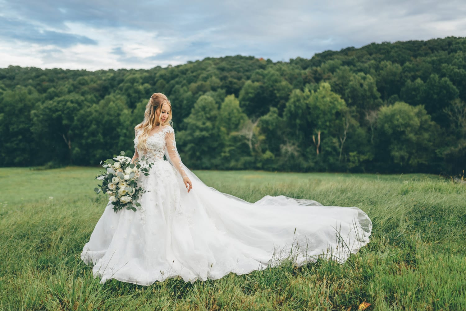 Bride poses in pasture with flowers