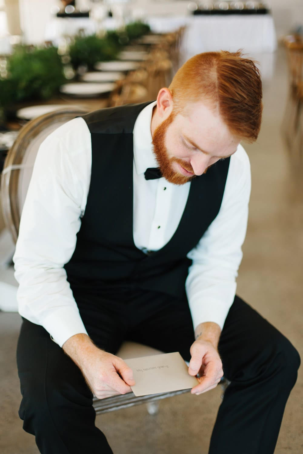 Groom reads letter in reception hall