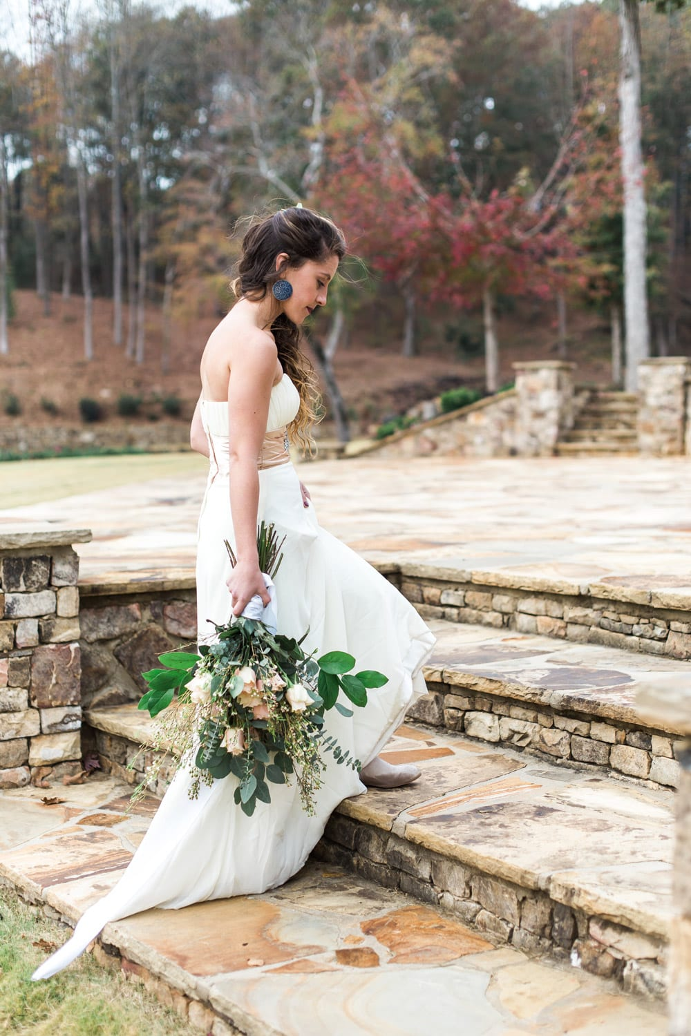 Bride walks with flowers on stone patio