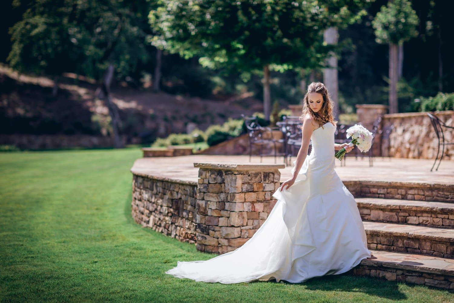 Bride poses with flowers by stone patio