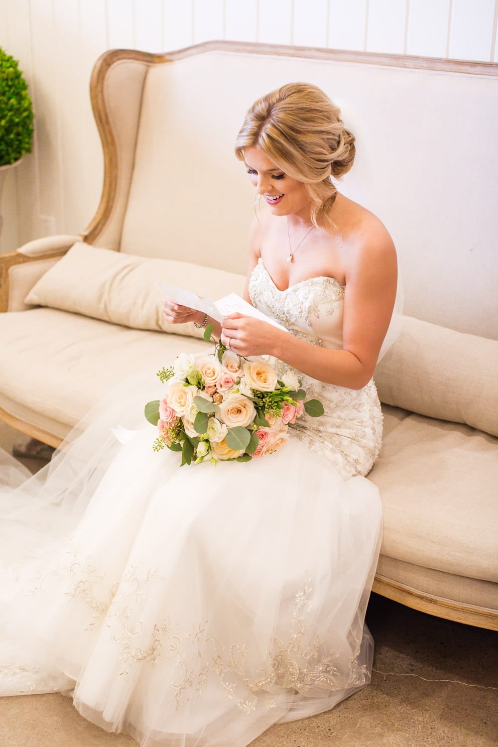 Bride reads letter on love seat