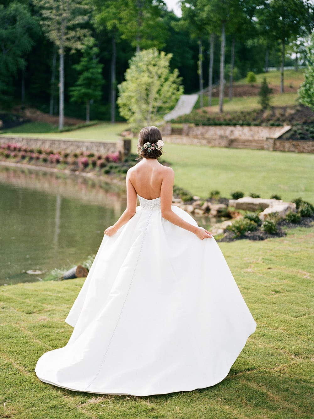 Bride walks outside along water