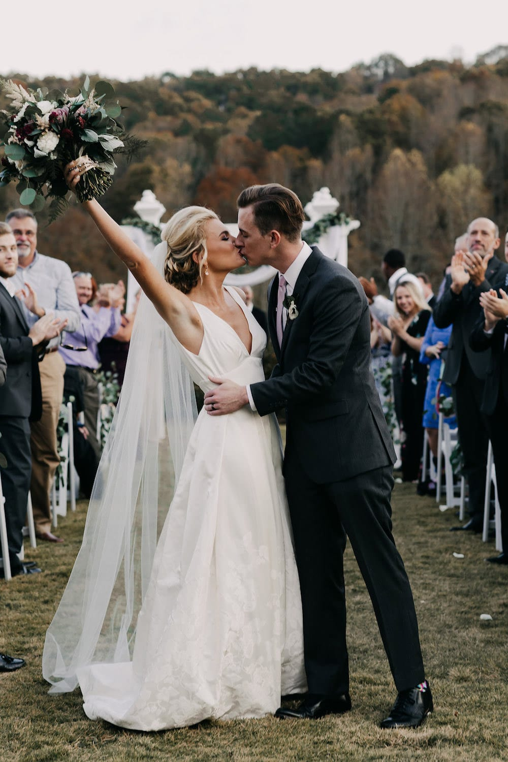 Bride and groom kiss on the aisle
