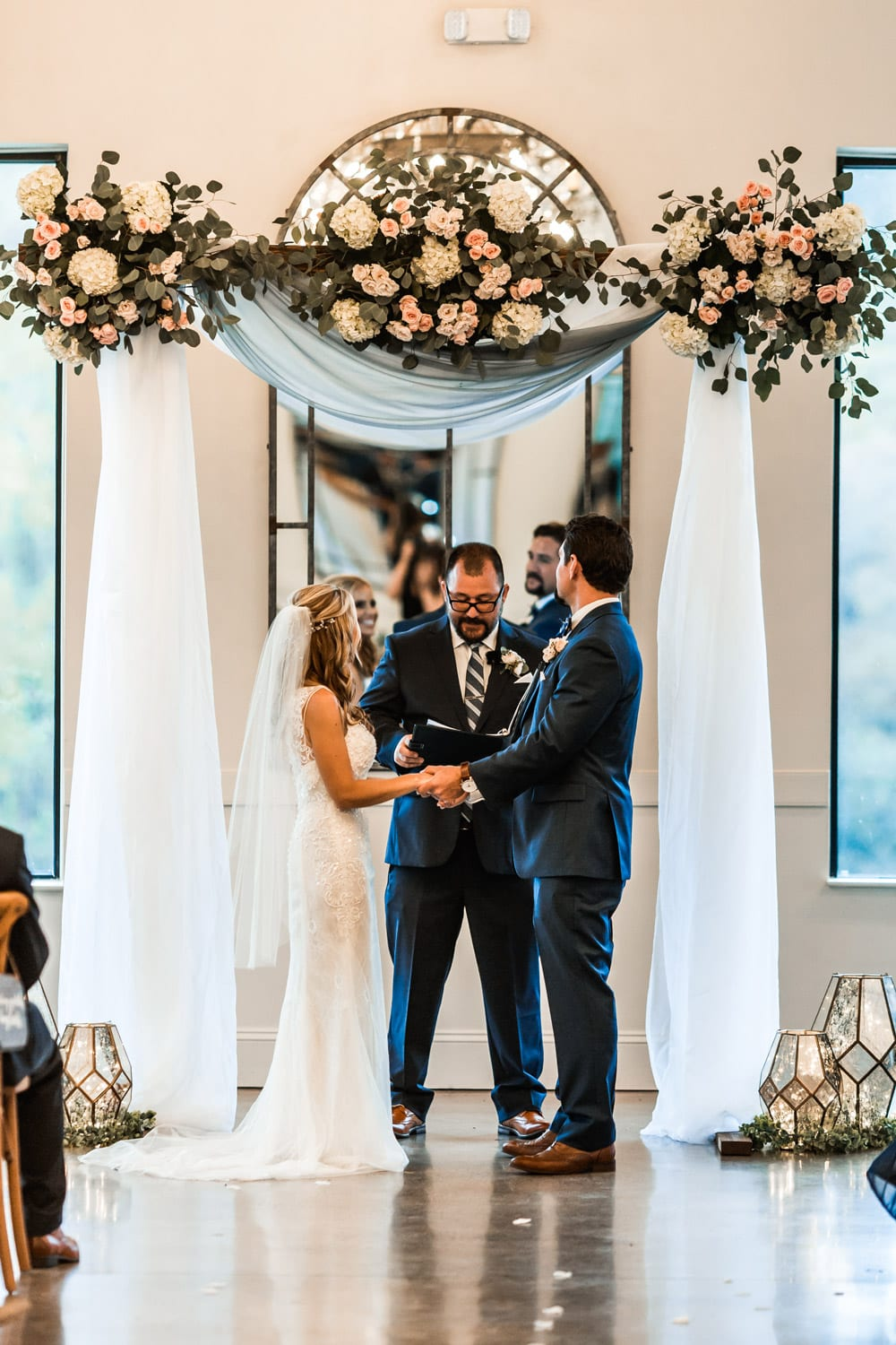 Bride and groom hold hands during indoor ceremony