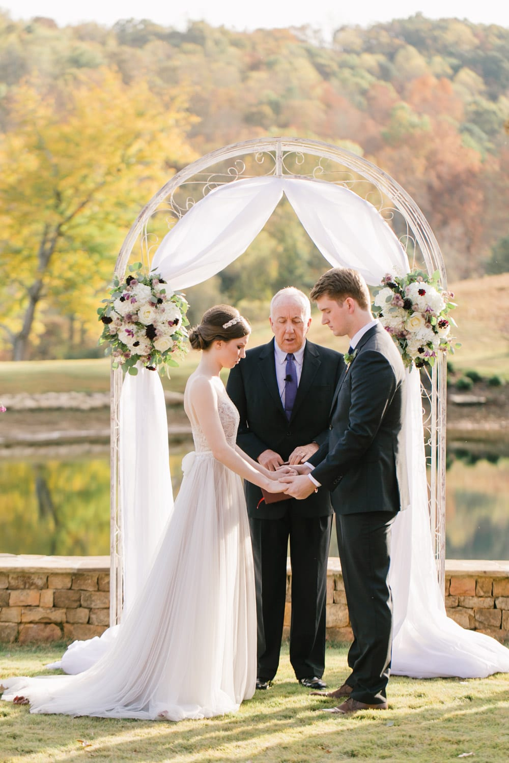 Bride and groom hold hands during outdoor ceremony