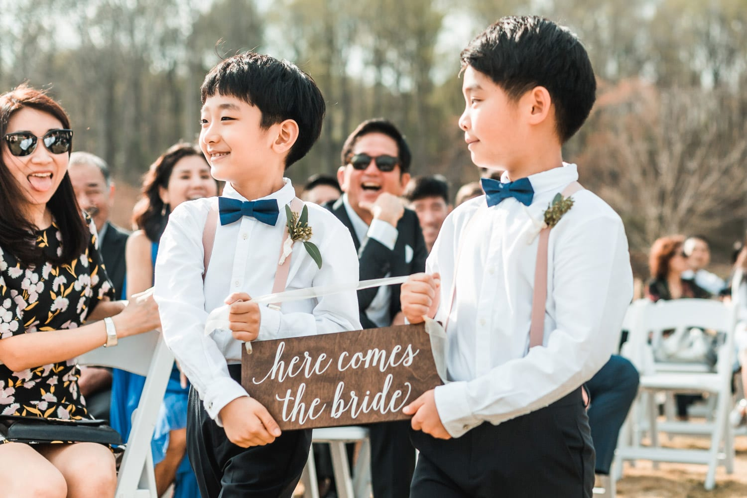 Two boys carry sign down the aisle