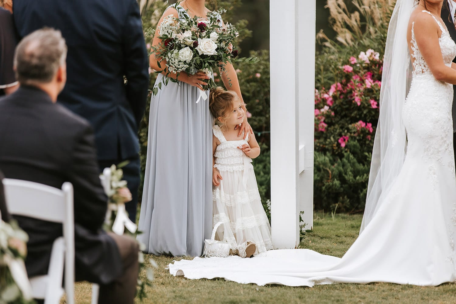 Flower girl looks up at bride during ceremony