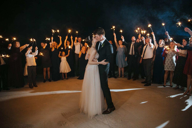 Groom kisses bride during send-off
