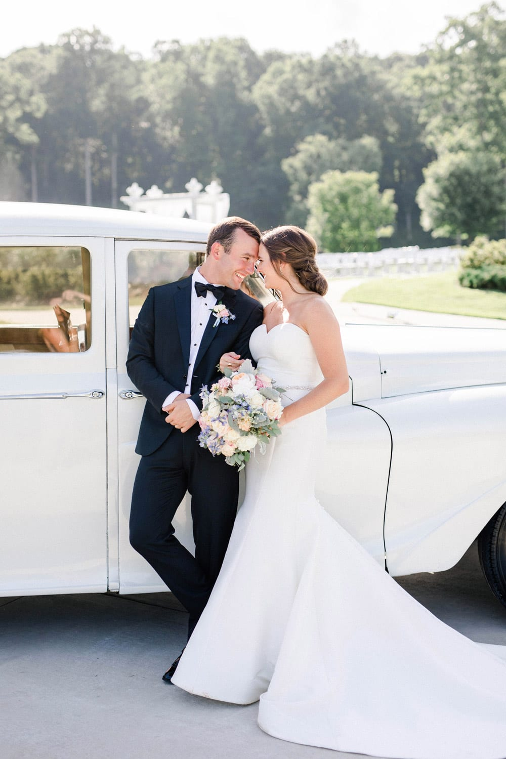 Bride and groom stand by car during send-off