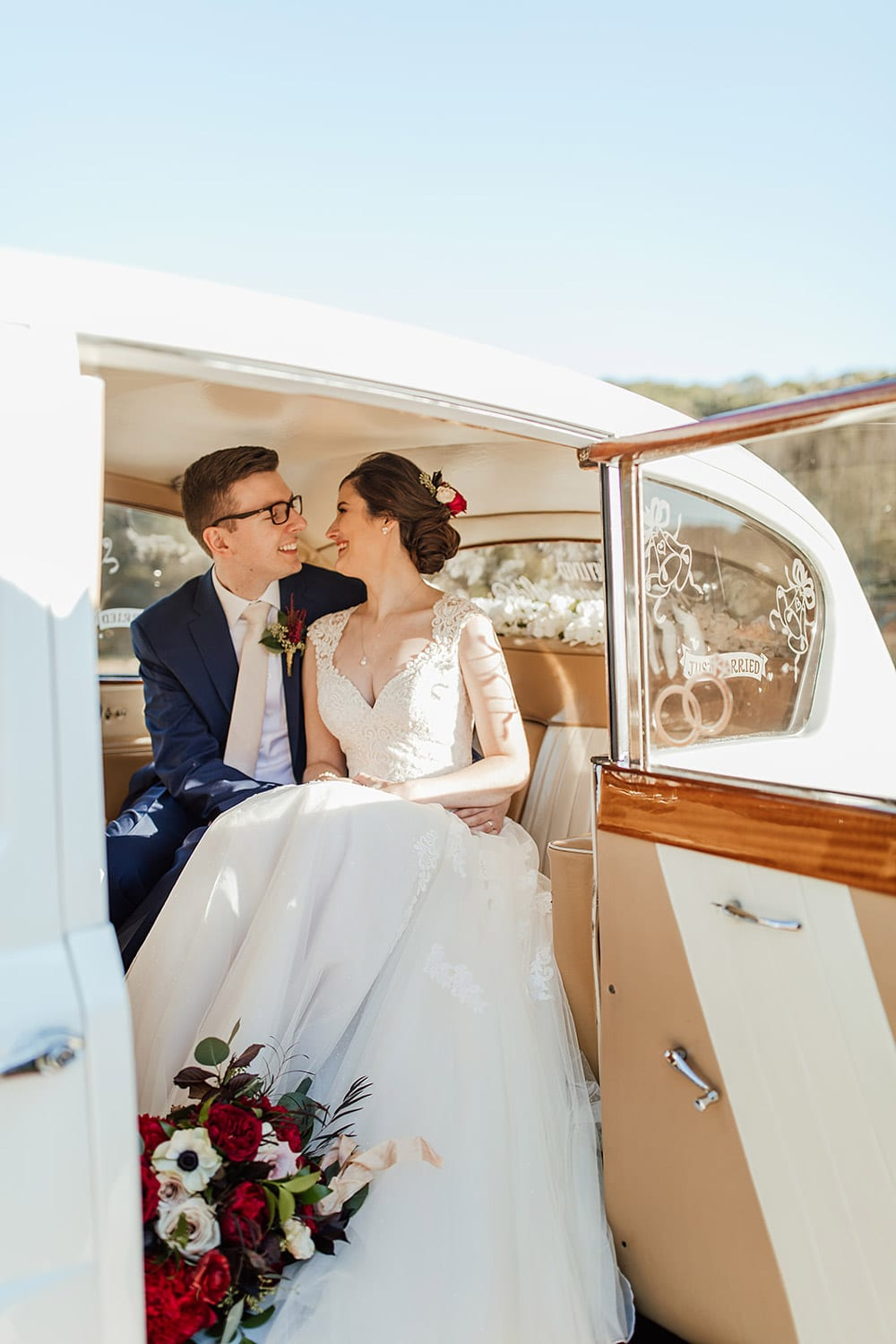 Bride and groom sit in car during send-off