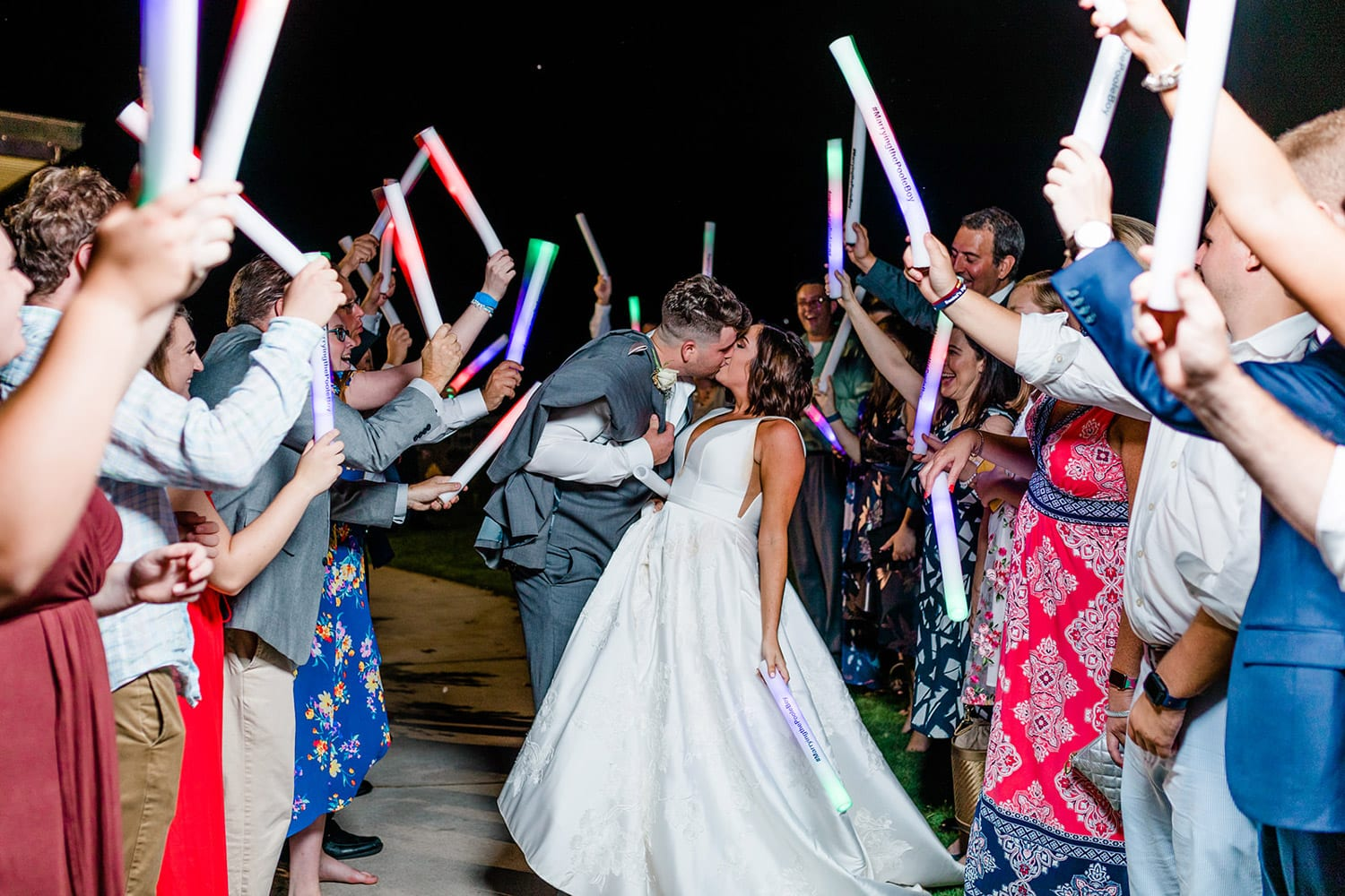 Groom kisses bride during send-off with glow sticks