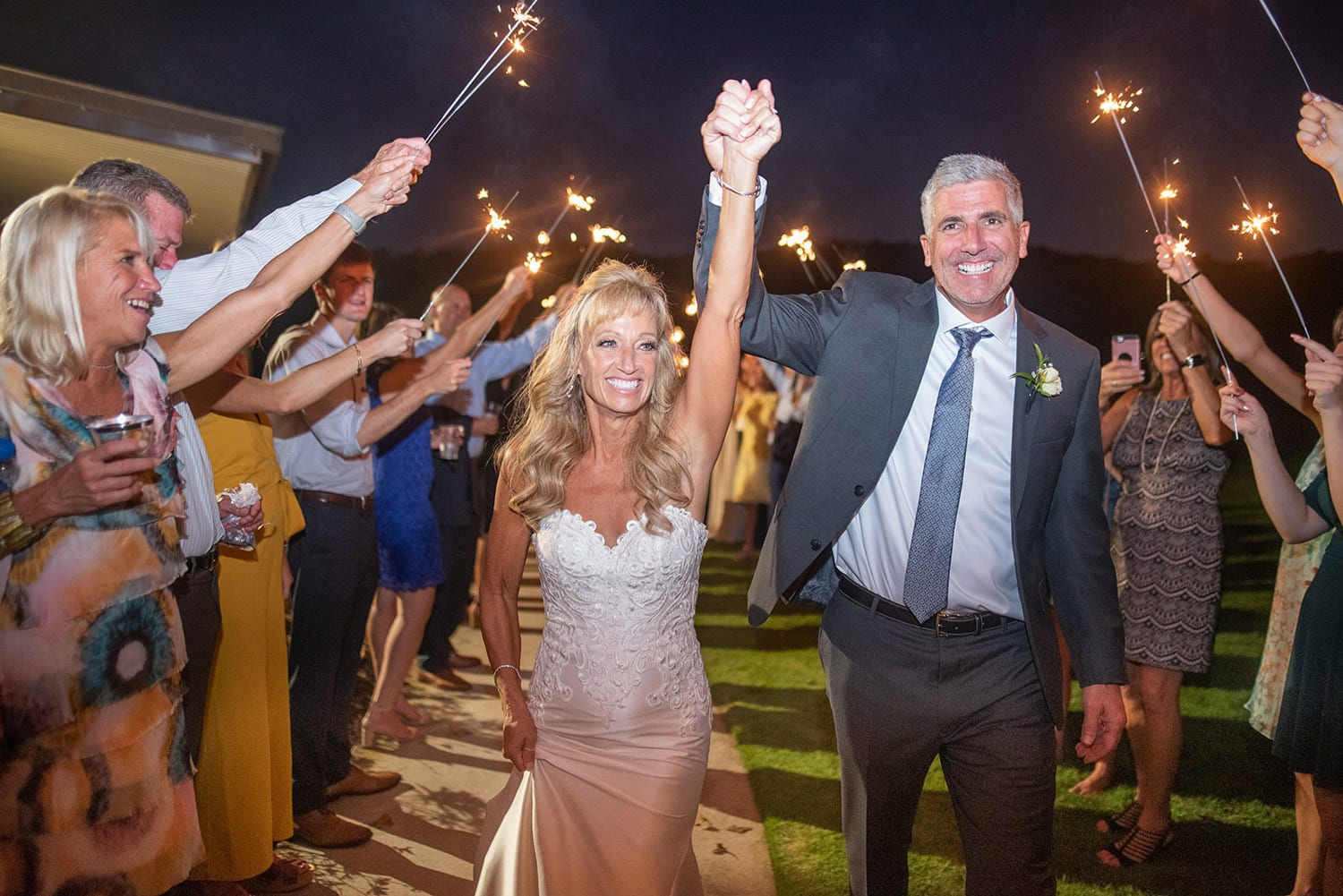 Groom and bride hold hands during send-off