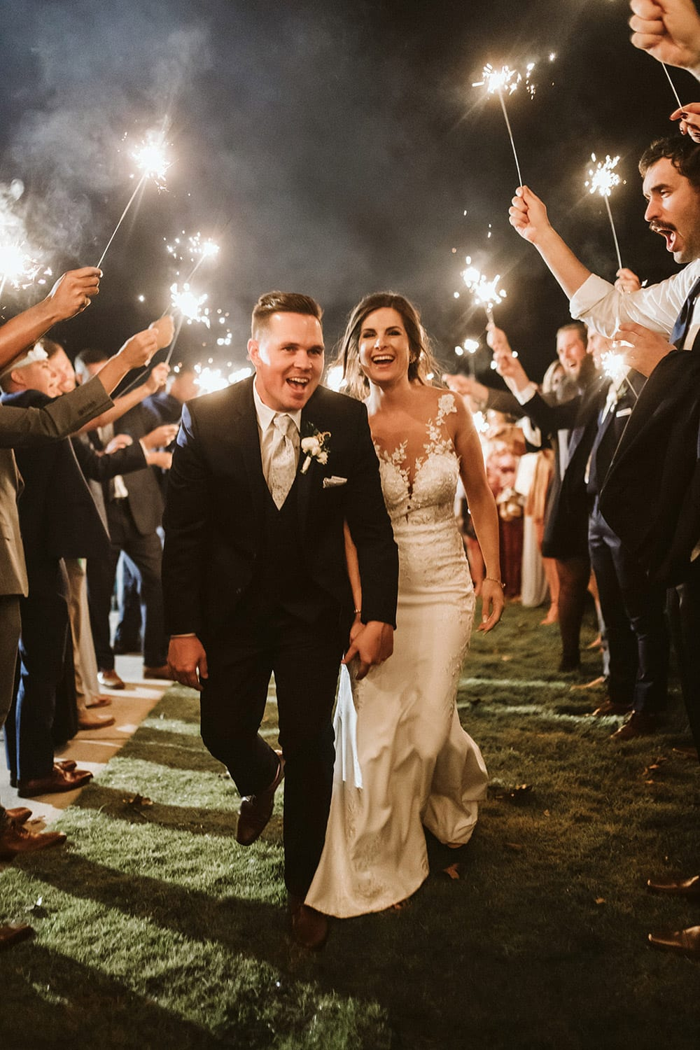 Groom and bride holding hands during send-off