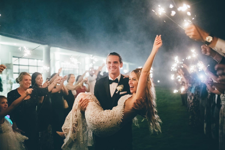 Groom carries bride during send-off