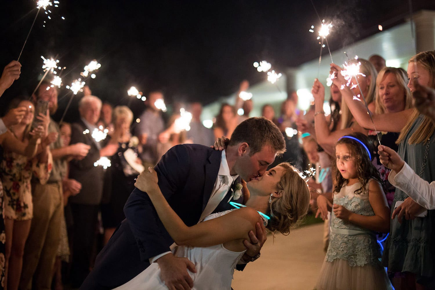 Groom kisses bride during send-off with color lights