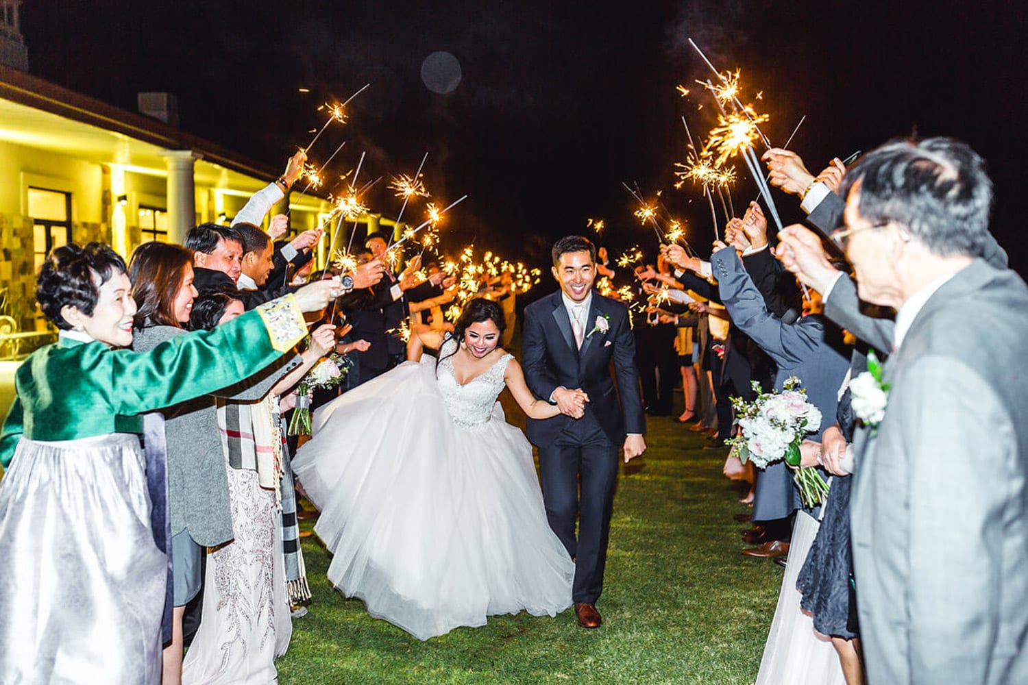Bride and groom hold hands during send-off