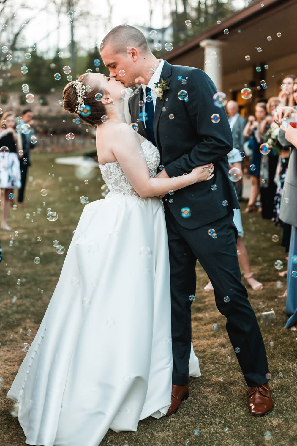 Bride and groom kiss surrounded by bubbles